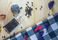 Black pepper. Organic black peppercorns in glass jar on wooden table Royalty Free Stock Photos