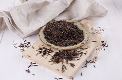 Organic black wild rice on a rustic ceramic plate on a white wooden background. Organic healthy black wild rice on a rustic ceramic plate with linen napkin and royalty free stock images