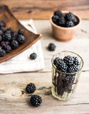 Organic blackberries in a glass on a gray wooden board, detox. Organic blackberries in a glass on a gray wooden board, rustic, detox,selective focus Royalty Free Stock Photography