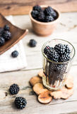 Organic blackberries in a glass on a gray wooden board, detox. Organic blackberries in a glass on a gray wooden board, rustic, detox,selective focus Stock Photography