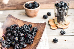 Organic blackberries in a glass on a wooden plate, rustic. Clean Royalty Free Stock Images
