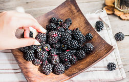 Organic blackberries in a glass on a wooden plate, rustic. Clean Royalty Free Stock Image