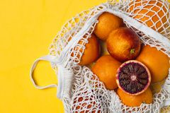 Organic bloody oranges in cotton mesh reusable bag, yellow background - recycling, sustainable lifestyle, zero waste, no plastic. Organic bloody oranges in stock image