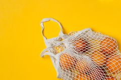 Organic bloody oranges in cotton mesh reusable bag, yellow background - recycling, sustainable lifestyle, zero waste, no plastic. Organic bloody oranges in stock photos