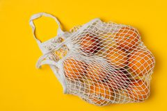 Organic bloody oranges in cotton mesh reusable bag, yellow background - recycling, sustainable lifestyle, zero waste, no plastic. Organic bloody oranges in royalty free stock photos