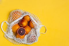Organic bloody oranges in cotton mesh reusable bag, yellow background - recycling, sustainable lifestyle, zero waste, no plastic. Organic bloody oranges in stock images