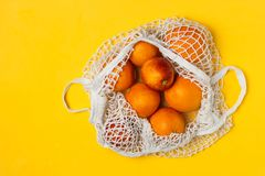 Organic bloody oranges in cotton mesh reusable bag, yellow background - recycling, sustainable lifestyle, zero waste, no plastic. Organic bloody oranges in royalty free stock image