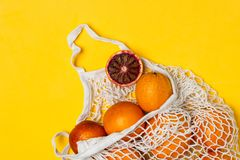 Organic bloody oranges in cotton mesh reusable bag, yellow background - recycling, sustainable lifestyle, zero waste, no plastic. Organic bloody oranges in stock photography