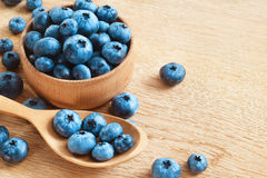 Organic blueberries in bowl on wooden background. Royalty Free Stock Photos