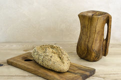 Organic bread over olive wooden cutting board and pitcher. Stock Photography