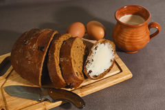 Organic breakfast or lunch in rural style. Sliced homemade rye brad with raisins and butter, two baked eggs and homemade yogurt in clay cup royalty free stock photo
