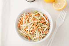 Organic broccoli slaw and shredded carrots. A white bowl of broccoli slaw shreded broccoli stalk and carrots  with lemons in the background, top view Stock Images