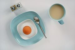 Organic brown egg breakfast. Farm fresh organic large brown egg with milky tea breakfast. Turquoise plate and mug shot from overhead in natural light royalty free stock images