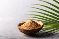 Organic Brown Palm Sugar In Coconut Bowl On Grey Concrete Background Stock Images