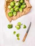 Organic Brussels sprouts Peeling with knife. On white wooden background Stock Image