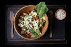Organic caesar salad in wodden bowl with caesar dressing. Intern Royalty Free Stock Photo