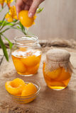 Organic canned peaches in glass jars with compote Stock Images