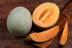 Organic cantaloupe with utensils on wooden table Stock Photos