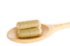 Organic capsule. Herb medical in wooden spoon. Stock Images
