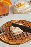 Organic carrot cake waffles with orange coconut cream. On a white, round plate with a knife and fork cutting through the waffle along with a clear glass bowl of royalty free stock photography