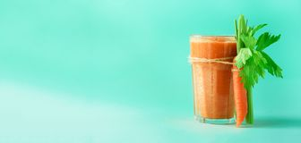 Organic carrot juice with carrots, celery on blue background. Fresh vegetable smothie in glass. Banner. Copy space. Summer food concept. Healthy detox eating royalty free stock photography