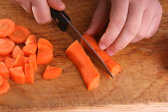 organic carrot, two hands and a knife Royalty Free Stock Images