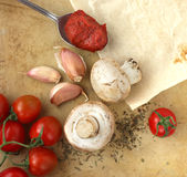 Organic cherry tomatoes, mushrooms, garlic and herbs on an old rustic stone chopping board. Still life composition from above. Pizza ingredients Stock Images