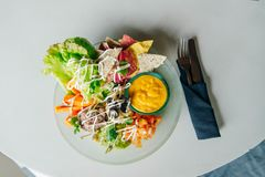 Organic chips with salad and sauce on a large plate stock images
