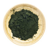 Organic chlorella powder. Nutrient-rich organic chlorella powder on a small ceramic bowl, isolated on white, top view Royalty Free Stock Image