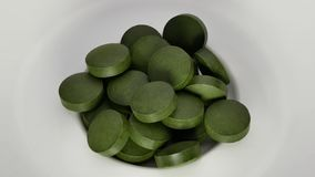 Spirulina,chlorella supplement pills on white. Selective focus stock video footage