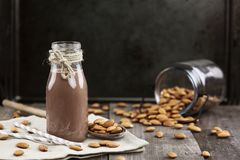 Organic Chocolate Almond Milk in a Jar. Organic chocolate  almond milk in a glass bottle with whole almonds spilled over a rustic wooden table Stock Photos