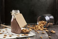 Organic Chocolate Almond Milk with Tag. In a glass bottle with whole almonds spilled over a rustic wooden table Stock Photo