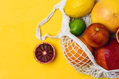 Organic citrus fruits variety in cotton mesh reusable shopping bag - recycling, sustainable lifestyle, zero waste, no plastic. Organic citrus fruits variety in stock photography