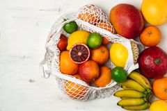 Organic citrus fruits variety in cotton mesh reusable shopping bag - recycling, sustainable lifestyle, zero waste, no plastic. Organic fruit variety in cotton stock photo
