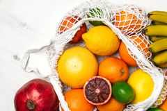 Organic citrus fruits variety in cotton mesh reusable shopping bag - recycling, sustainable lifestyle, zero waste, no plastic. Organic fruit variety in cotton royalty free stock image