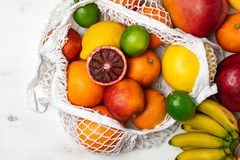 Organic citrus fruits variety in cotton mesh reusable shopping bag - recycling, sustainable lifestyle, zero waste, no plastic. Organic fruit variety in cotton royalty free stock photography
