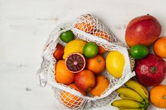 Organic citrus fruits variety in cotton mesh reusable shopping bag - recycling, sustainable lifestyle, zero waste, no plastic. Organic fruit variety in cotton stock image