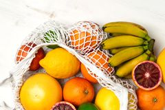 Organic citrus fruits variety in cotton mesh reusable shopping bag - recycling, sustainable lifestyle, zero waste, no plastic. Organic fruit variety in cotton stock photography