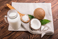 Organic coconut milk in mason jar, fresh exotic coconuts fruit and wooden spoon with coconut chips on a wooden background. Exotic coconut milk in a mason jar Stock Image