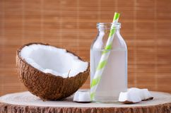 Organic coconut water in a glass jar with tubule on natural background. Organic coconut water in a glass jar with tubule on brown Stock Photography