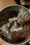 Organic Coffee Beans Roasting in an Industrial Coffee Bean Roaster and Cooling on Mechanical Stirring Pan. Inside royalty free stock image