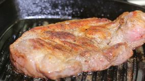 Organic cooked fried pork chop steak meat with on black frying pan close up view stock footage