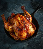 Organic cornfed free range oven baked chicken in rustic pan with lemon slices and rosmary Royalty Free Stock Photography