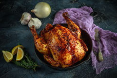 Organic cornfed free range oven baked chicken in rustic pan with lemon slices and rosmary Stock Photo