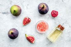 Organic cosmetic set with fresh fig, bath salt, oil and scrub on stone background flat lay Royalty Free Stock Photo