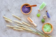 Cosmetic set with wheat herbs and sea salt in bottle on stone table background flat lay Royalty Free Stock Image