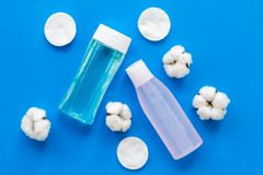 Facial tonic, lotion and cotton pads for face care on blue background top view mock up. Organic cosmetics for face clearing. Facial tonic, lotion and cotton pads stock image