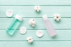 Facial tonic, lotion and cotton pads for face care on mint green wooden background top view mock up. Organic cosmetics for face clearing. Facial tonic, lotion royalty free stock photo