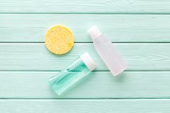 Facial tonic, lotion and sponge for face care on mint green wooden background top view mock up royalty free stock image