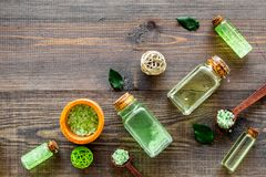Organic cosmetics with tea tree oil and spa salt on dark wooden background top view copyspace Royalty Free Stock Photo
